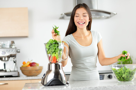 of shake: Green smoothie woman making vegetable smoothies with blender home in kitchen. Healthy eating lifestyle concept portrait of beautiful young woman preparing drink with spinach, carrots, celery etc. Stock Photo