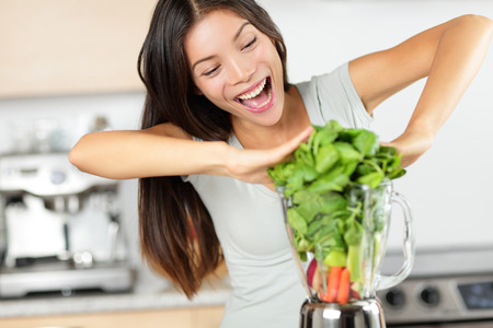 summer diet: Vegetable smoothie woman making green smoothies with blender home in kitchen. Healthy raw eating lifestyle concept portrait of beautiful young woman preparing drink with spinach, carrots, celery etc. Stock Photo