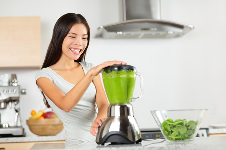 Vegetable smoothie woman blending green smoothies with blender home in kitchen. Healthy eating lifestyle concept portrait of beautiful young woman preparing drink with spinach, carrots, celery etc. Stock Photo