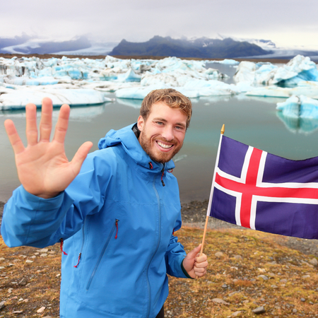 icelandic flag: Islandia turista mostrando la bandera de Islandia por Jokulsarlon. Hombre caminante feliz celebraci�n que muestra la bandera de Islandia en frente del glaciar lago  laguna glaciar. Feliz masculino sonriente en concepto de turismo.