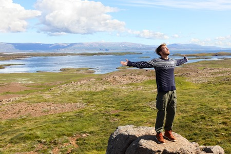 Freedom man in nature on iceland happy with arms enjoying free happiness in beautiful icelandic landscape.  Male hiker relaxing in nature. photo