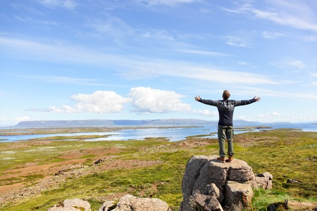Freedom man in nature on iceland with arms enjoying free happiness in beautiful icelandic landscape.