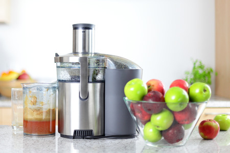 Apple juice on juicer machine - juicing concept. Apples in bowl in kitching and fresh pressed juice.