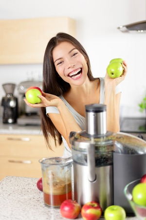 Apple juice - Woman making apple juice on juicer machine at home in kitchen. Juicing and healthy eating happy woman making green vegetable and fruit juice. Mixed race Asian Caucasian model. Stock Photo