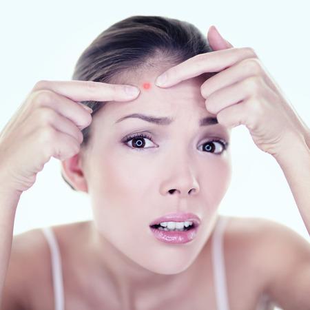 pubertad: El acné espinilla piel chica cuidado de la piel mancha mancha. Chica de belleza en el rostro presionando problema de la piel. Mujer con la piel mirando mancha en el espejo aislado. Modelo asiático joven hermosa hembra de raza caucásica.