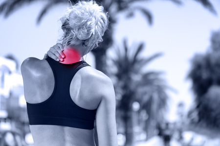 chronic back pain: Neck pain. Athletic running woman with injury in sportswear rubbing touching upper back muscles outside after exercising and training. Stock Photo