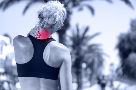 Nekpijn. Atletische lopende vrouw met letsel in sportkleding te wrijven ontroerende bovenrug spieren buiten na het trainen en opleiding.