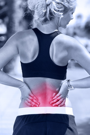 spinal disc herniation: Back pain. Athletic running woman with injury in sportswear rubbing touching lower back muscles outside after exercising and training. Stock Photo