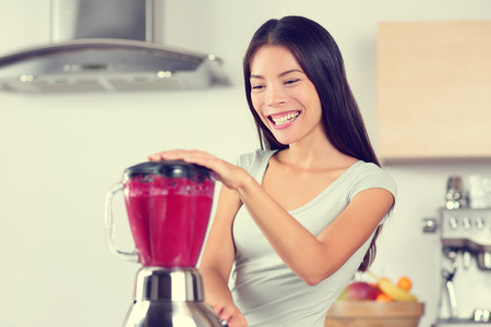 beet juice: Smoothie woman making fruit smoothies with blender. Healthy eating lifestyle concept portrait of beautiful young woman preparing drink blending strawberries, raspberries and berries home in kitchen. Stock Photo