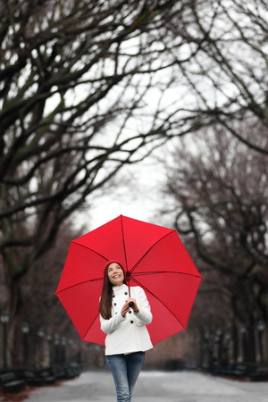 Umbrella woman walking in Central Park in winter  fall daydreaming. Happy smiling multiracial dreamer girl walking cheerful with red umbrella in Central Park, Manhattan, New York City, USA. photo