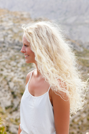 blonde haired: Blonde woman with long hair smiling happy. Blond long haired beautiful young female model smiling happy in profile outdoors on beach. Caucasian girl.