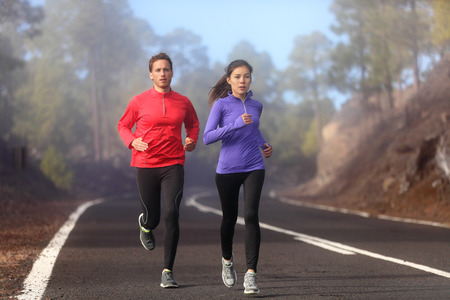 Healthy running runner man and woman workout on mountain road. Jogging male and female fitness model working out training for marathon on forest road in amazing nature landscape. Two runners execising
