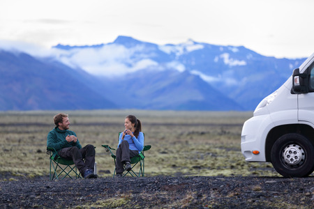 Travel couple by mobile motor home RV campervan. People sitting in chairs relaxing camping and enjoying traveling on Iceland in recreational vehicle. Young couple enjoying coffee in nature landscape. Stock Photo
