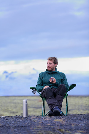 folding chair: Camping man sitting in folding chair drinking coffee from bottle flask at dusk in nature on Iceland. Camper relaxing thinking pensive taking break on road trip in beautiful Icelandic nature.