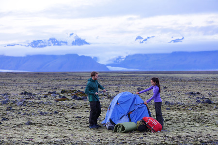 camping pitch: Camping couple pitching tent after hiking. Friends putting up tent for the night after hike with gear and backpacks. Active lifestyle image with Caucasian man and Asian woman.