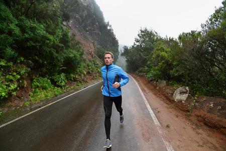 Hombre corredor correr y correr por la carretera en la lluvia en la chaqueta y medias largas. Ajuste, hombre modelo de la aptitud que se resuelve vivir entrenamiento estilo de vida saludable para el maratón. Modelo caucásico joven de unos 20 años.