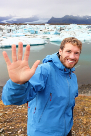 Tourist waving hand by Jokulsarlon on Iceland on travel. Portrait of happy man saying hello smiling looking at camera front of the glacial lake  glacier lagoon. photo
