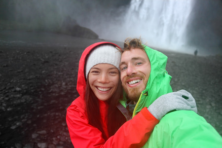 Selfie couple taking smartphone picture of waterfall outdoors in front of Skogafoss on Iceland. Couple visiting famous tourist attractions and landmarks in Icelandic nature landscape on Ring Road. Stock Photo