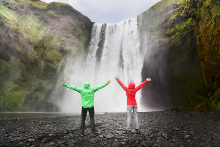 icelandic: People by Skogafoss waterfall on Iceland golden circle. Couple visiting famous tourist attractions and landmarks in Icelandic nature landscape. Stock Photo
