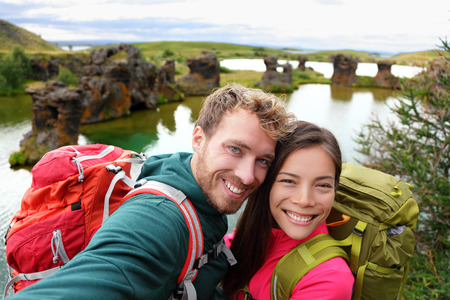 iceland: Selfie - travel couple on lake Myvatn Iceland. Friends taking selfies photo having fun traveling together visiting Icelandic tourist destination landmarks. Lake Myvatn lava columns, Iceland. Stock Photo