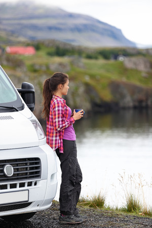 Travel woman by mobile motor home RV campervan. Traveler relaxing camping and enjoying traveling on Iceland in recreational vehicle. Girl enjoying coffee in Icelandic nature landscape.