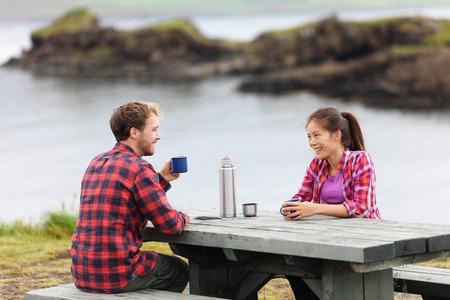 アイスランドの湖によって魔法瓶フラスコから飲むコーヒー テーブルに座ってキャンプのカップル。キャンパーの女と男の撮影をリラックス美しい 写真素材