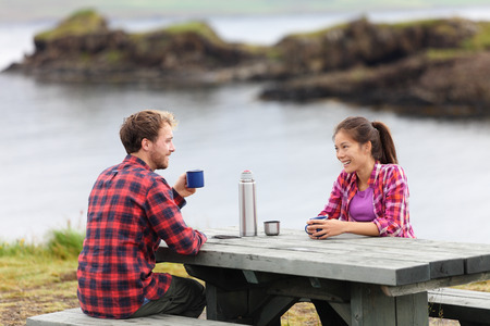 Camping couple sitting at table drinking coffee from thermos bottle flask by lake on Iceland. Campers woman and man relaxing taking break on road trip in beautiful Icelandic nature.