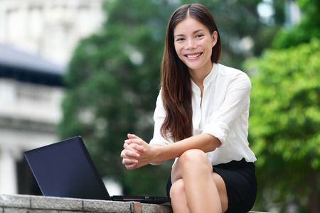 3g: Business people - woman on laptop in Hong Kong. Businesswoman on computer and internet outside in Central Hong Kong. Young female professional business woman smiling. Asian Chinese Caucasian woman.