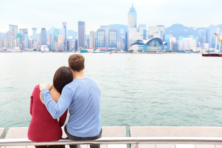 Hong Kong skyline and Victoria harbour. Couple tourists enjoying view and sightseeing on Tsim Sha Tsui Promenade and Avenue of Stars in Victoria harbour, Kowloon, Hong Kong. Tourism travel concept. Stock Photo