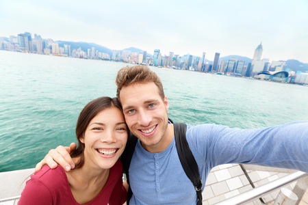 sha: Selfie - Tourists couple taking selfportrait picture photo in Hong Kong enjoying sightseeing on Tsim Sha Tsui Promenade and Avenue of Stars in Victoria Harbour, Kowloon, Hong Kong. Travel concept.