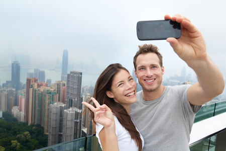 Hong Kong Victoria Peak tourists couple taking selfie photo picture with smartphone enjoying view over Hong Kong and Victoria Harbour. Young happy multiethnic couple traveling in Asia. Stock Photo