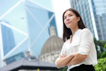Business woman confident portrait in Hong Kong. Businesswoman standing proud and successful in suit cross-armed. Young multiracial Chinese Asian  Caucasian female professional in central Hong Kong. Stock Photo