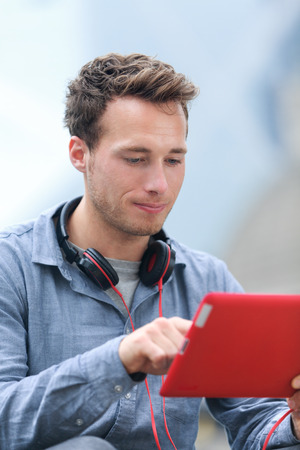 late 20s: Urban young professional man using tablet computer sitting outside using app on 4g wireless device wearing headphones. Casual young urban professional male in his late 20s.