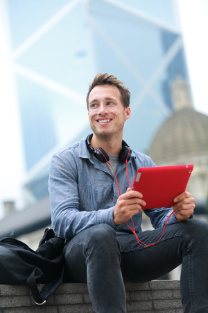 late 20s: Urban young professional man using tablet computer sitting in Hong Kong outside using app on 4g wireless device wearing headphones. Casual young urban professional male in his late 20s.