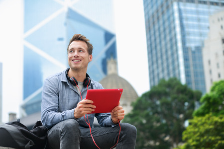 late 20s: Urban man using tablet computer sitting in Hong Kong outside using app on 4g wireless device wearing headphones. Casual young urban professional male in his late 20s. Hong Kong Central. Stock Photo