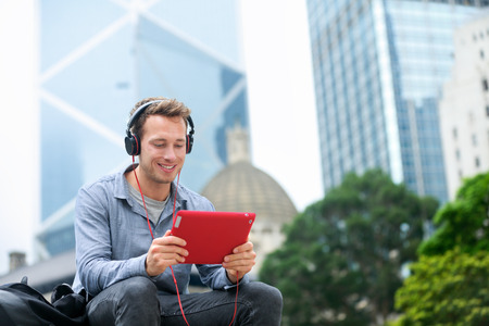 skype: Man talking on tablet pc having video chat conversation in sitting outside using app on 4g wireless device wearing headphones. Casual young urban professional male in his late 20s. Hong Kong. Stock Photo