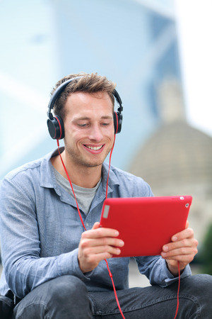 late 20s: Video chat conversation. Man talking on tablet pc sitting outside using app on 4g wireless device wearing headphones. Casual young urban professional male in his late 20s.