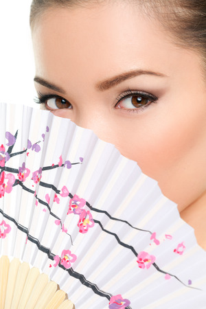 eye close up: Asian beauty - seductive eyes woman chinese or japanese. Eye makeup Asian look with paper fan. Beauty portrait of mixed race Asian  Caucasian female model on white background. Close up on eyes.