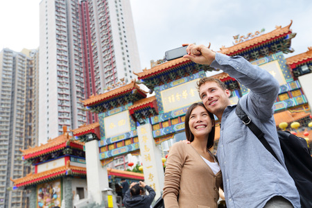 hong kong street: Hong Kong tourist attraction Wong Tai Sin Temple. Tourists taking selfie photo pictures by famous Hong Kong landmark. Romantic couple visiting and sightseeing Taoist temple. Asian woman, Caucasian man