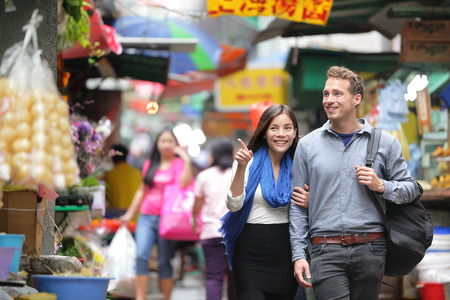 Turystów na zakupy na ulicy rynku w Hongkongu. Para chodzenia rozglądać się w sklepach. Asian kobieta, mężczyzna rasy kaukaskiej.