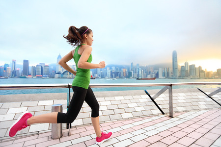hongkong: City Running - woman runner and Hong Kong skyline. Female athlete fitness athlete jogging training living healthy lifestyle on Tsim Sha Tsui Promenade and Avenue of Stars in Victoria Harbour, Kowloon. Stock Photo