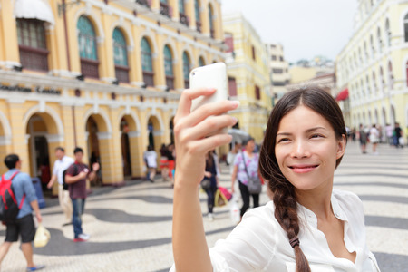 the senate: Woman tourist taking selfie pictures in Macau, China in Senado Square or Senate Square. Asian girl tourist using smart phone camera to take photo while traveling in Macau. Travel and tourism concept.