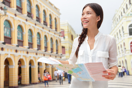 macao: Tourist holding travel map in Macau. Woman visiting Macau, China for sightseeing looking for directions at tourists map smiling happy on Senado Square or Senate Square.
