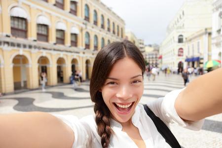macau: Selfie woman taking fun selfportrait in Macau, China in Senado Square or Senate Square. Asian girl tourist using smart phone camera to take photo while traveling in Macau. Travel and tourism concept. Stock Photo
