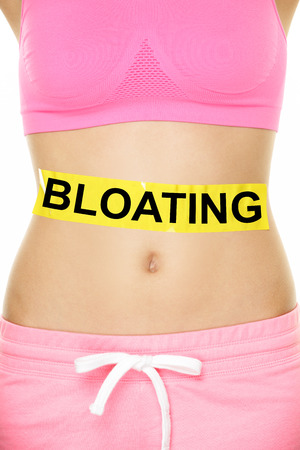 flatulence: Bloating in stomach abdomen. BLOATING text written on female stomach. Bloated due to food diet conceptual image.