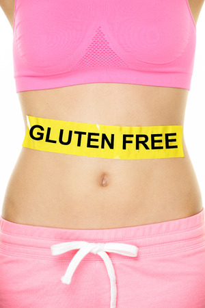 celiac: Gluten free health and Celiac disease and digestion concept with GLUTEN FREE text written on stomach abdomen sign on woman belly. Conceptual food allergies image.