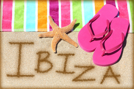 ibiza: Ibiza beach travel concept background. IBIZA written in sand with water next to beach towel, summer sandals and starfish. Summer and sun vacation holidays on Balearic Islands, Spain.