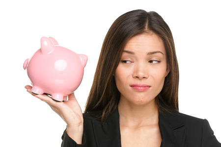 savings problems: Piggy bank savings with unhappy funny woman looking displeased at pink piggy bank isolated on white background. Business woman or banker wearing suit jacket. Mixed race Asian Caucasian female model.