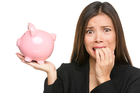 investing: Money stress - business woman holding piggy bank. Debt, bankruptcy and savings concepts with stressed female businesswoman biting nails nervous isolated
