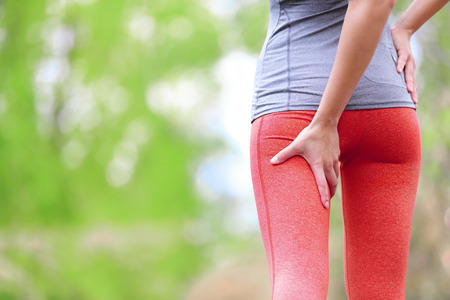 ハムスト リングの捻挫またはけいれん。女性ランナーとランニングのスポーツの傷害。女性バック太もものクローズ アップ。